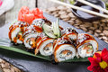 Sushi rolls set with salmon, cream cheese, cucumber, sesame and wasabi on black stone on bamboo mat, selective focus. Royalty Free Stock Photo