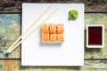Sushi rolls in white plate seafood with chopsticks and japanese spices Royalty Free Stock Images
