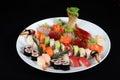 Sushi and sashimi mixed on round white plate Royalty Free Stock Photo