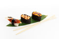 Sushi set on banana leaves on a white background with chopsticks Royalty Free Stock Images