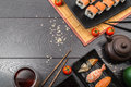 Sushi set sashimi and sushi rolls and tomatoes served on dark background Royalty Free Stock Photo