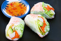 Sushi spring rolls delicious salad served with sweet chili sauce on black plate Stock Photo