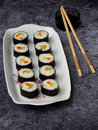 Sushi on white plate, grey background. Traditional Asian food. Diet healthy food.