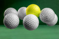 Suspended golf balls six white and one yellow in mid air on a green bacground Stock Photos