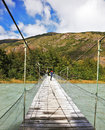 Suspension bridge across mountain river in the middle of the woman tourist photographs the raging torrent Royalty Free Stock Image