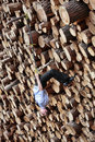 Suspension workout on the large pile of cut wooden logs caucasian man business casual Royalty Free Stock Image
