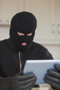 Suspicious burgler holding tablet pc in kitchen Royalty Free Stock Photography