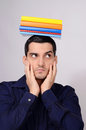 Suspicious student holding a pile of books on his head raising his eyebrow funny teacher with colorful over looking to the side Royalty Free Stock Image