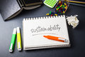 Sustainability on the desk with handwriting of word in notebook Royalty Free Stock Photography