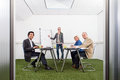 Sustainability strategy meeting small business with four people in a small stylish conference room with grass on the floor Royalty Free Stock Photo
