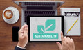 Sustainability on the tablet pc screen held by businessman hands online top view Royalty Free Stock Images