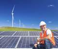 Sustainable clean energy technician with solar panels and wind turbines Stock Photos