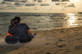 Swain sitting together on the beach and watching sunset, romance Royalty Free Stock Photo