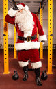 Sweating tired santa claus having break in training in gym Royalty Free Stock Photography