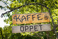Swedish cafe sign hanging from a chain with trees at the background Stock Photos
