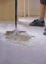 Sweeping the floor with a broom man sweeps Royalty Free Stock Image