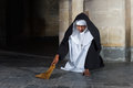 Sweeping nun the floor of a medieval abbey with a hand brush Royalty Free Stock Photo