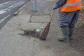 Sweeping and pushing a broom road sweeper cleaning walkway with made of twigs Royalty Free Stock Photography