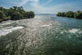 Sweeping view of niagara river rushing with tree lined banks and blue sky Royalty Free Stock Photo