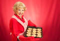 Sweet adorable grandmother holding pan freshly baked chocolate chip cookies photographed over red background room text Royalty Free Stock Photo