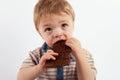 Sweet baby boy eating a chocolate bar Royalty Free Stock Photo