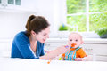 Sweet baby boy eating his first solid food witn hi young attractive mother feeding her cute son giving him healthy vegetable pure Royalty Free Stock Image