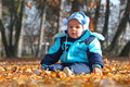 Sweet baby boy sitting in autumn park Royalty Free Stock Photography