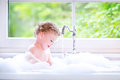 Sweet baby girl playing with foam in big kitchen sink funny little wet curly hair taking a bath a lots of water drops and splashes Stock Image