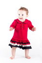 Sweet baby girl in red dress making her first steps Royalty Free Stock Photo