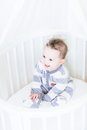 Sweet baby girl sitting in a round white bassinet little Stock Photography