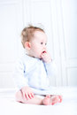 Sweet baby girl sucking on her finger sitting in a white nursery wearing blue knitted dress Royalty Free Stock Photography