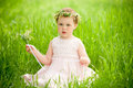 Sweet baby girl in wreath of flowers sitting on green grass Royalty Free Stock Photo