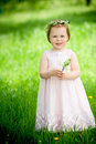 Sweet baby girl in wreath of flowers smiling outdoors Royalty Free Stock Photography