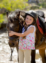 Sweet beautiful young girl 7 or 8 years old hugging head of little pony horse smiling happy wearing safety jockey helmet in summer