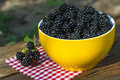 Sweet blackberry in bowl on wooden table Royalty Free Stock Image