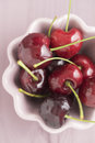 Sweet cherries in bowl on pale pink wooden table Royalty Free Stock Photo