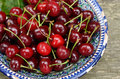 Sweet cherry in blue oriental bowl ripe uzbek plate over rusted wooden background Stock Photos