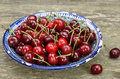 Sweet cherry in blue oriental bowl ripe uzbek plate over rusted wooden background Stock Images