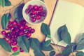 Sweet cherry and notebook for daily records berries of ripe lie in a white plate rasspypana on a wooden surface nearby a Stock Images