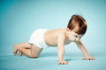 Sweet child crawls blue background Royalty Free Stock Photo