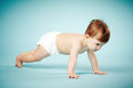Sweet child crawls blue background Royalty Free Stock Image