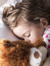 Sweet child sleeping with teddy bear baby girl in bed Stock Image
