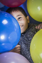 Sweet child surrounded by balloons at a party fun Stock Photos