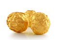 Sweet chocolate candy wrapped in golden foil isolated on white background Stock Photos