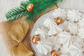 Sweet christmas background with airy meringues ,fir branch,golden acorns and knot Royalty Free Stock Photo