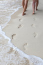 The sweet couple holding hands walking on beach and their footpr footprints in sand around seashore Stock Photos