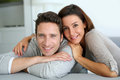 Sweet couple at home looking at camera portrait of sitting in sofa Stock Images