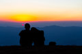 Sweet couple silhouette sitting on the mountain with sunset Royalty Free Stock Photo