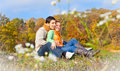 Sweet couple sitting on a hill at the autumn landscape and looking Stock Images
