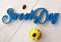 Sweet day letters and one cupcake on white table Stock Images